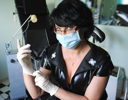 Domina Linda Dorn im Latexoutfit und mit Mundschutz zieht ihre Gummihandschuhe an