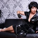 Domina Linda Dorn liegt auf einer schwarzen Couch, hält eine Gerte und deutet nach unten streng