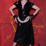 Mistress Linda Dorn trägt ein enges Latexkleid hält ein Bondageseil in beiden Händen vor sich vor rotem Hintergrund