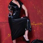 Mistress Linda Dorn trägt ein enges Latexkleid, hält eine Handschelle vor sich und stellt einen Fuß auf umgeworfenen Stuhl vor rotem Hintergrund