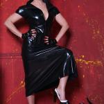 Mistress Linda Dorn trägt ein enges Latexkleid, schaut streng beide Hände an die Hüfte haltend und stellt einen Fuß auf umgeworfenen Stuhl vor rotem Hintergrund