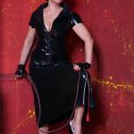 Mistress Linda Dorn trägt ein enges Latexkleid, schaut streng, hält eine Bullenpeitsche und stellt einen Fuß auf umgeworfenen Stuhl vor rotem Hintergrund