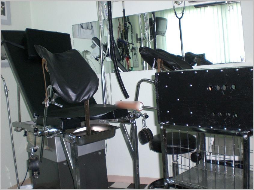Im Klinikraum der Gynokologiestuhl und davor die Dildo-Maschine