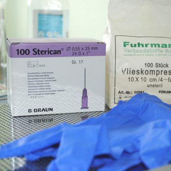 Blaue Latexhandschuhe und im Hintergrund 100 sterile Nadelverpackung und 10 Vlieskompressen in der Verpackung