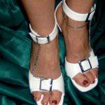 Die rot lackierten Füße von Domina Linda Dorn in weißen Sandaletten