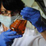 Fetisch Ärztin untersucht Urin im Laborglas mit blauen Latex Handschuhen mit Mundschutz
