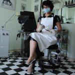 Fetisch Ärztin Linda Dorn sitzt schwarz-weißem Latex Outfit vor ihren Untersuchungsraum