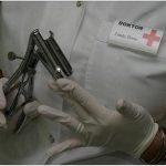 Oberkörper von Doktor Linda Dorn im weißen Kittel und weißen Handschuhen hält ein Metall Gerät für anale Untersuchung in der Hand haltend