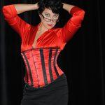 Domina Linda Dorn in roter Bluse, rot schwarzem Korsett und engen schwarzem Mini-Rock in Pose mit beiden Händen am Kopf