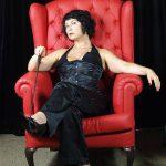 Domina Linda Dorn sitzt ganz in schwarz angezogen, streng schauen mit Gerte in der Hand im rotem Sessel
