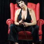 Domina Linda Dorn sitzt nach vorne gebeugt, ganz in schwarz angezogen, streng schauen mit Gerte in der Hand im rotem Sessel