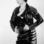 Vor einer weissen Wand steht Domina Linda Dorn mit kürzeren Haaren in einem Lack Outfit mit sehr großen Nieten verziert, im Seitenprofil da