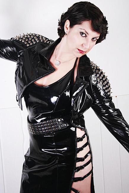 Vor einer weissen Wand steht Domina Linda Dorn mit kürzeren Haaren in einem Lack Outfit mit sehr großen Nieten verziert, schräg da