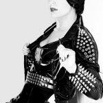 Vor einer weissen Wand steht Domina Linda Dorn mit kürzeren Haaren in einem Lack Outfit mit sehr großen Nieten verziert