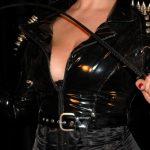 Der Oberkörper in Lack mit sehr vielen großen, stacheligen Nieten zu sehen mit einer gebogenen Gerte in beiden Händen fest umschlossen von Domina Linda Dorn aus Frankfurt