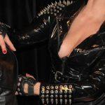 Oberkörper von Domina Linda Dorn im Lackoutfit mit vielen großen Nieten hält eine Kopf