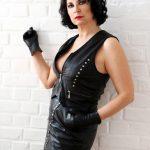 Domina Linda Dorn steht streng vor weißer Backsteinwand im schwarzen Lederkostüm