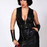 Mistress Linda Dorn steht strenger Pose mit Lederkleidung vor einem weißem Hintergrund