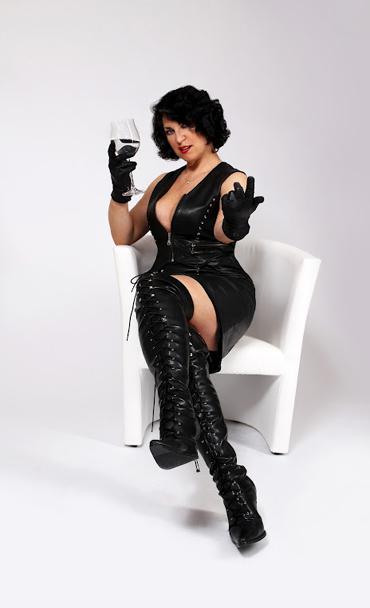 Fetisch Domina Linda Dorn sitzt im engen schwarzem Lederoutfit im weißen Sessel vor weißem Hintergrund Wein trinkend und fordert mit einem Grinsen auf, her zu kommen