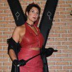 Porträt von Fetisch Domina Linda Dorn, die streng mit kurzen Haaren im roten Lederoutfit mit Gerte vorm Andreaskreuz steht