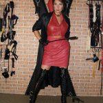 Fetisch Domina Linda Dorn steht streng mit kurzen Haaren im rot schwarzem Lederoutfit mit Gerte vorm Andreaskreuz