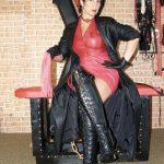 Fetisch Domina Linda Dorn sitzt mit kurzen Haaren im rot schwarzem Lederoutfit streng mit Peitsche dar
