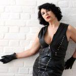 Domina Linda Dorn steht lasziv vor weißer Backsteinwand im schwarzen Lederkostüm