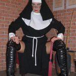 Domina Linda Dorn im Nonnenkostüm sitzt mit gespreizten Beinen und Peitsche in der Hand und schaut einen streng an