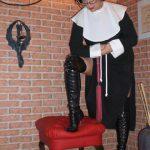 Fetischdomina Linda Dorn schaut stehend im Nonnenkostüm vorwurfsvoll herab mit einem Fuß auf rotem Sessel