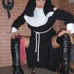 Fetischdomina Linda Dorn als strenge Nonne sitzend mit roter Peitsche in der Hand