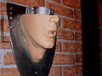 Besondere Wandekoration: Auf einer Metallplatte ist vom Hals bis zur Nase ein Gesicht, auf der Platte liegt ein Eisenring
