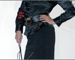Domina Linda Dorn von Brust bis Knie mit schwarzer Fetisch Uniform und Peitsche in der Hand