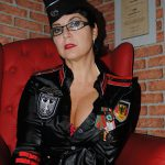 Porträt-Foto von Domina Linda Dorn in schwarzer Uniform streng schauend und im Sessel sitzend