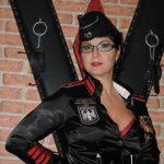 Porträt-Foto von Domina Linda Dorn in schwarzer Uniform vorm Andreaskreuz