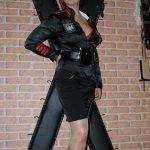 Domina Linda Dorn steht in schwarzer Uniform vorm Andreaskreuz