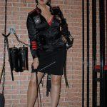 Domina Linda Dorn steht streng in Uniform mit Gerte zum Boden zeigend